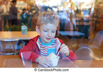 boy eating ice-cream - cute cheerful little boy eating...