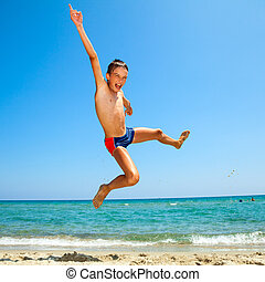 Boy jumping on the beach