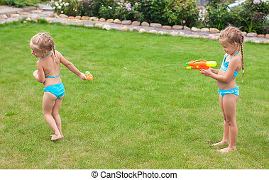 Two little adorable girls playing with water guns in the...