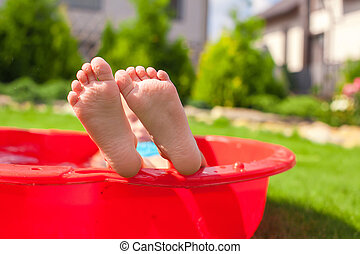 Closeup of little kids legs in small red pool