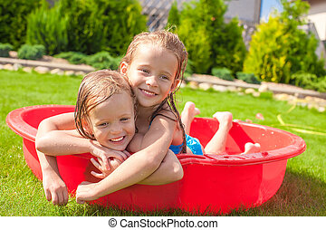 Two little sisters playing and splashing in the pool on a...