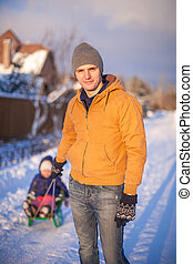 Young father sledding his little daughter on a sled in the snow outdoors