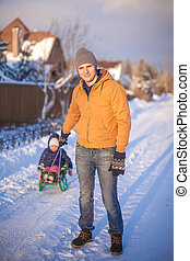 Young father sledding his little daughter on a sled in the...