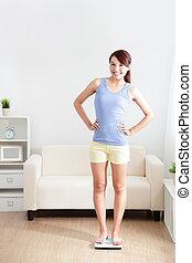 Woman smiling and standing on weighing scales at home, asian
