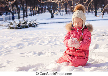 Adorable little girl have fun outdoor on cold winter day