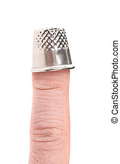Metal sewing thimble on finger. Isolated on a white...
