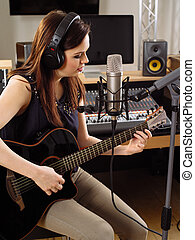 Woman with guitar in a recording studio