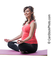 Smiling pretty pregnant woman meditating in studio