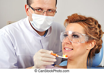 Dentist shows toothbrush - Dentist shows a patient how to...