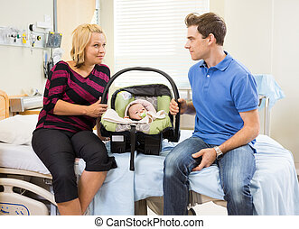 Couple With Baby Looking At Each Other On Hospital Bed