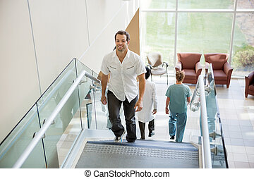 Patient And Medical Team Walking On Stairs In Hospital