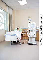 Renal Dialysis - Young male patient sleeping while receiving...