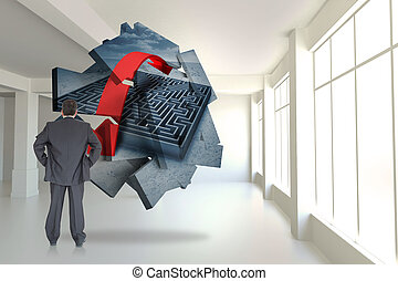 Businessman standing back to the camera with hands on hip  against maze graphic on abstract screen in room