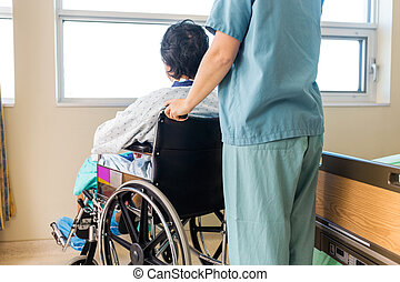 Nurse Holding Patient's Wheelchair's Handle By Window -...