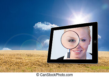 Businesswoman holding magnfying glass on tablet screen...