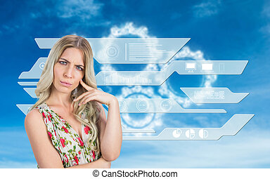 Frowning pretty blonde wearing flowered dress posing against...