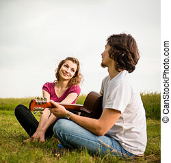 Playing guitar - dating couple - Young man playing to his...