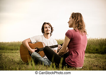 Playing guitar - dating couple - Young man playing guitar to...