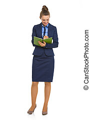 Full length portrait of business woman writing in notepad
