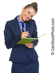 Happy business woman talking mobile phone and writing in notepad