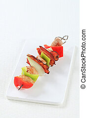 Meat and vegetable skewer on cutting board