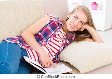 Young woman reading book - Smiling young woman reading...