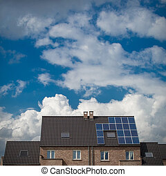 New houses with solar panels on roof under blue sky and clouds