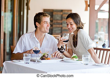 At Restaurant - A young couple sitting at a table at an...