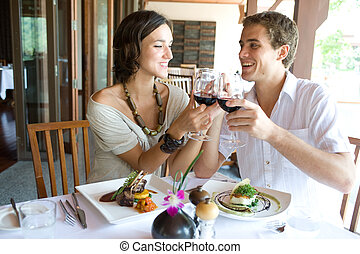 Couple At Dinner - A young couple sitting together in a...
