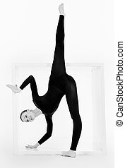 silhouette - Modern ballet dancer posing with a cube at...