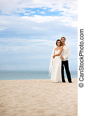 Bride and Groom - A bride and groom standing on beach