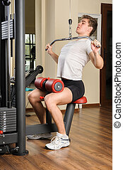 Young man doing lats pull-down workout in gym - Handsome...