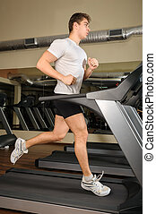 young man running at treadmill in gym - young handsome man...