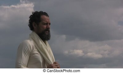 Arabian man standing in front of beautiful clouds