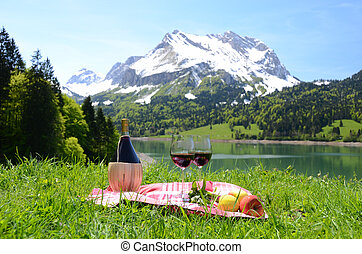 Wine and vegetables served at a picnic in Alpine meadow....