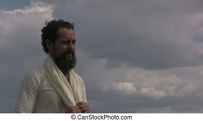 Arabian man standing in front of clouds