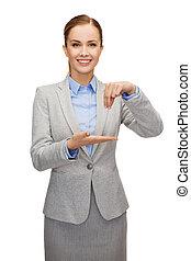 smiling businesswoman holding something imaginary -...