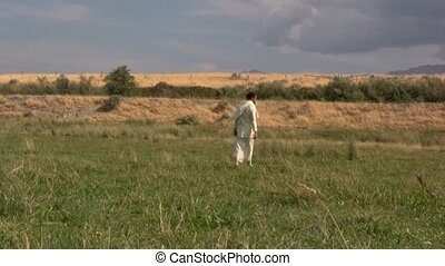 Arabian man standing in a field of green grass