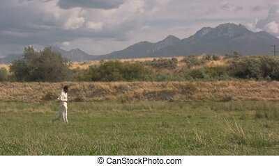 Arabian man walking across a grass field