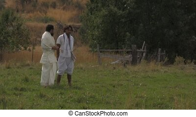 Arabian men standing and talking in a field wind blowing