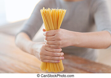 close up of female hands holding spaghetti pasta - cooking,...