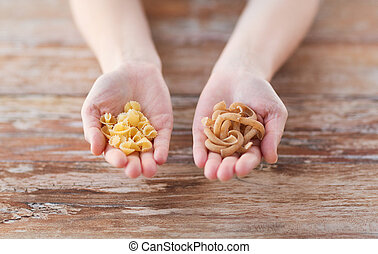 female hands with different pasta variations - cooking, food...