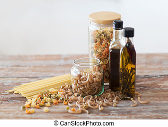 close up of two olive oil bottles and pasta in jar - cooking...