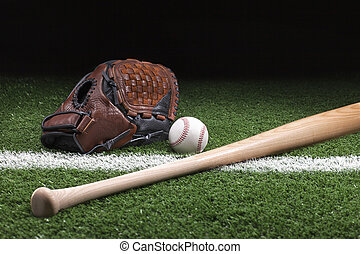 Baseball with mitt and bat on green grass at night -...