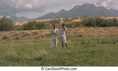 Arabian men standing in a grass field wind blowing