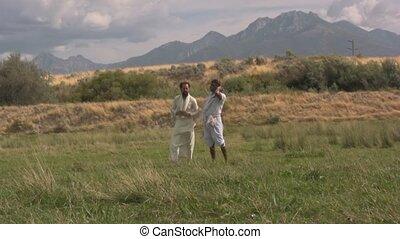 Arabian men standing in a grass field wind blowing