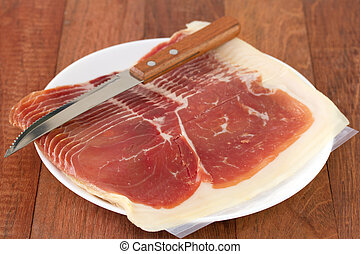 prosciutto with knife on white plate