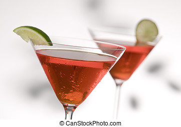 two red martinis with lime, focus is on front glass