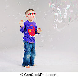 Little man playing with soap bubbles - Little child playing...