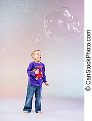Cute little boy enjoying soap bubbles - Cute little boy...